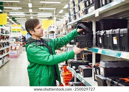 Man buying toolbox in supermarket