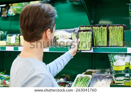 Man buys a asparagus in the store - stock photo