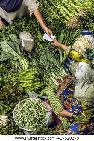 Man buys food in traditional asian market. - stock photo