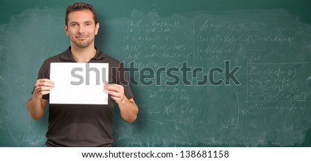 Man by a blackboard with math operations holding a blank sign - stock photo