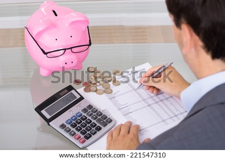 Man calculating savings and costs. Over the shoulder view - stock photo