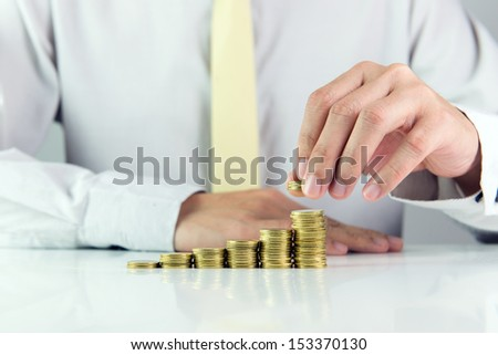 Man calculating stack of gold coins in one row - stock photo