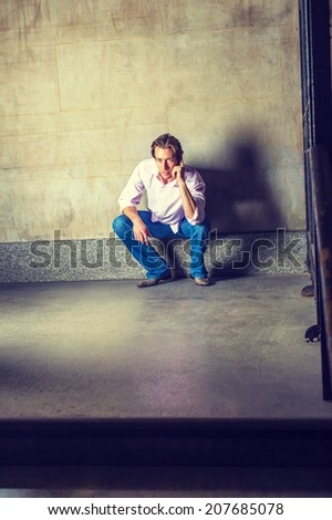 Man Calling on Phone. Wearing a light pink, long sleeve shirt, blue jeans, leather shoes, a young businessman is squatting in the corner of the gate, making a phone call on his cell phone. - stock photo