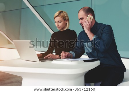Man calling with mobile phone while his assistant searching needed information on laptop computer, two confident business workers using net-book and cell telephone for the development of joint project - stock photo