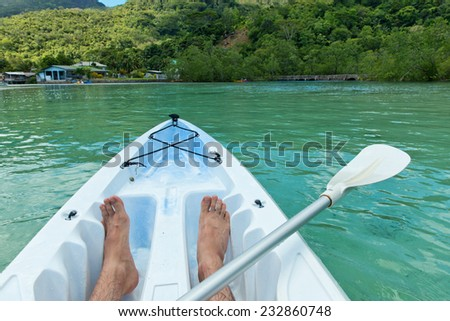 Man canoeing in the Seychelles off the coast of Mahe island near Port Launay, view of his bare feet and paddle in the bows - stock photo
