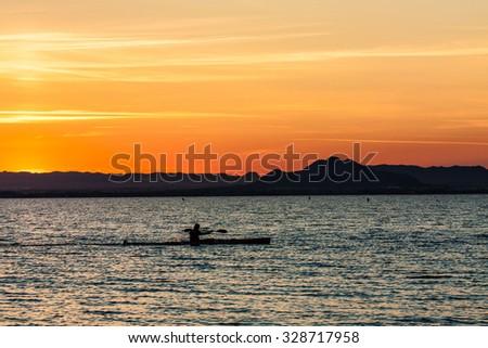 Man canoeing on sunset view - stock photo