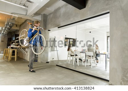 Man carrying a bicycle in the office - stock photo