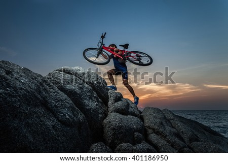 Man carrying a bike on the shoulder on the rock during sunset - stock photo
