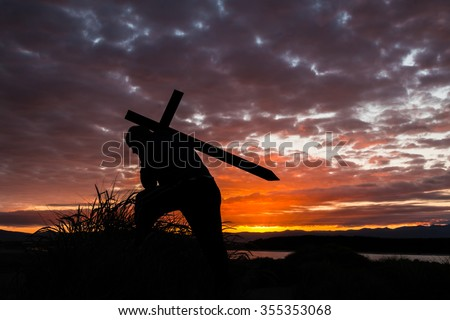 Man carrying a cross up a hill at sunrise. - stock photo