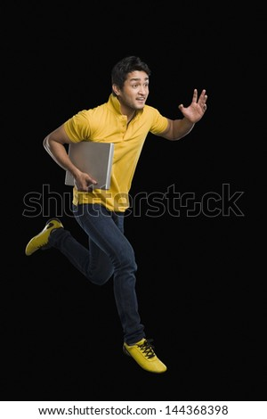 Man carrying a laptop and smiling - stock photo