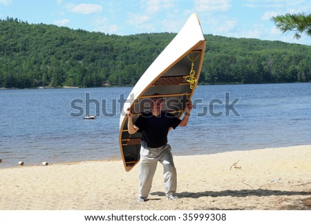 Man carrying a large canoe on a beach