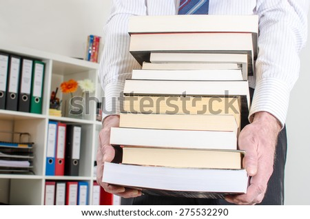 Man carrying a pile of books at office - stock photo
