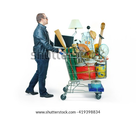 man carrying a shopping cart full of things - stock photo