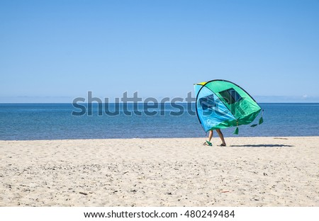 Man Carrying a Tent on the Beach