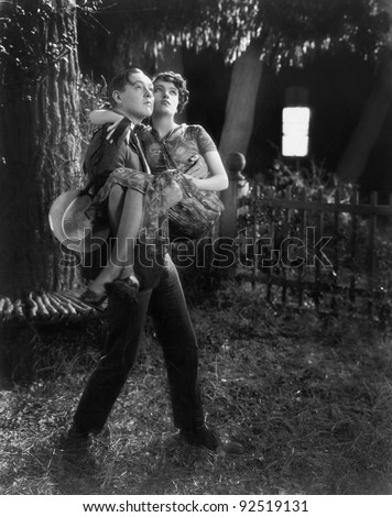 Man carrying a woman in his arms through a backyard