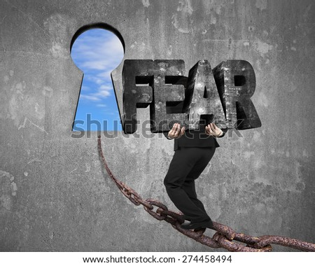 Man carrying big 3D fear concrete word walking on old iron chain toward keyhole door, with sky clouds view and gray concrete wall background - stock photo