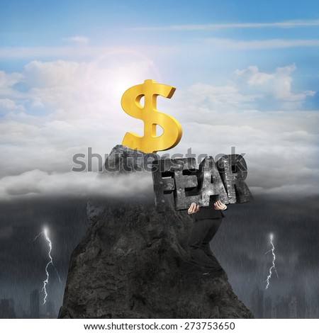 Man carrying 3d fear mottled concrete word, climbing toward golden dollar sign on mountain peak, with opposite weather conditions, sunny sky cloudscape, dark overcast lightning raining cityscape - stock photo