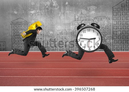 Man carrying dollar sign and running after alarm clock of running legs, on red track with concrete wall background. - stock photo