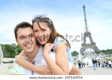 Man carrying girlfriend on his back in front of Eiffel tower - stock photo