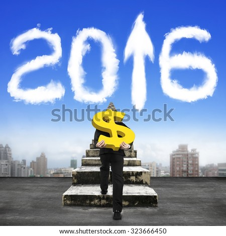 Man carrying golden dollar sign climbing old concrete stairs toward white 2016 shape clouds in sky. - stock photo