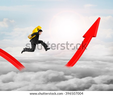 Man carrying golden dollar sign running on growing red arrow graph, on sky cloudscape background. - stock photo
