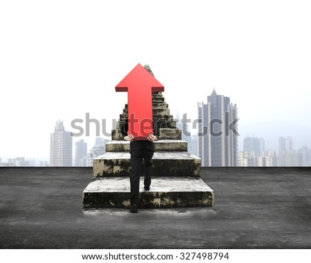 Man carrying red arrow up sign climbing old concrete stairs, with city skyscraper background - stock photo