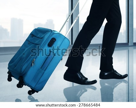 Man carrying suitcase walking through the airport hallway - stock photo