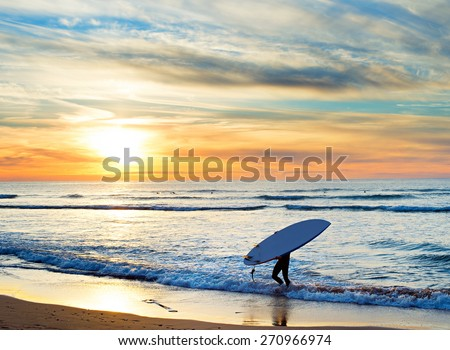 Man carrying surfboard on the beach at sunset. Sagres, Algarve region, Portugal - stock photo