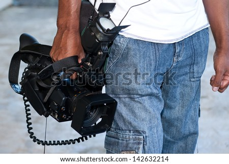Man carrying video camera - stock photo