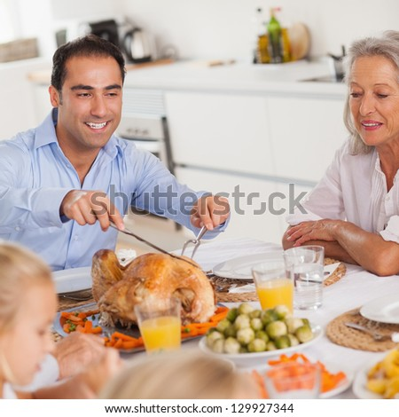 Man carving the thanksgiving turkey at head of table - stock photo