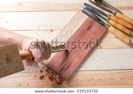 Man carving wood with handtools