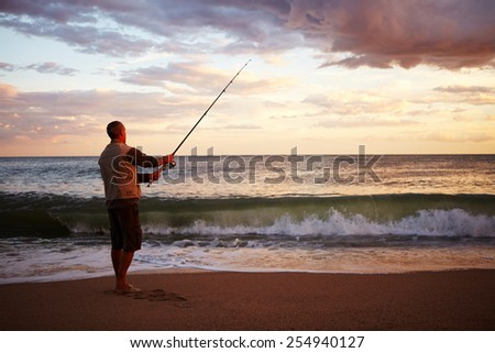 Man casting a fishing line into ealry morning surf