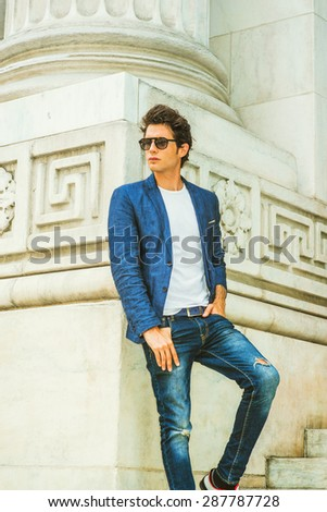 Man Casual Fashion. Dressing in blue blazer, white under shirt, jeans, wearing sunglasses, a young European college student standing by column on campus in New York, looking away. Instagram effect. - stock photo