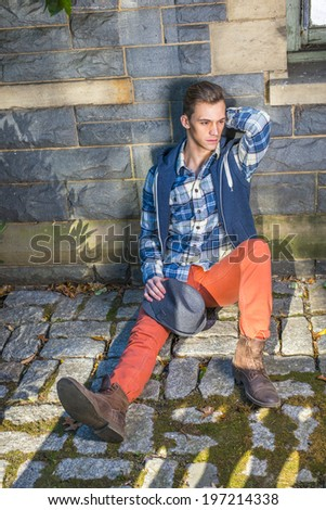 Man Casual Fashion. Dressing in blue, white pattern shirt, a hoody vest,  red jeans, leather boot shoes, holding a woolen Fedora hat on his knee, a young guy is sitting on the ground, thinking.