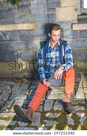 Man Casual Fashion. Dressing in blue, white pattern shirt, a hoody vest,  red jeans, leather boot shoes, holding a woolen Fedora hat, a young guy is sitting on the ground against wall, thinking.