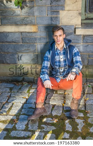 Man Casual Fashion. Wearing a blue and white pattern shirt,  a blue hood vest,  red jeans, brown leather boot shoes, a young guy is sitting on the ground against the wall with ivy leaves, relaxing.