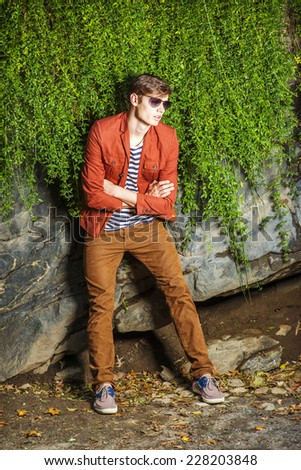 Man Casual Fashion. Wearing a dark reddish brown jacket, striped under shit, brown corduroy pants, sneakers, sunglasses, a young guy standing by rocks wall with long leaves, crossing arms, relaxing.