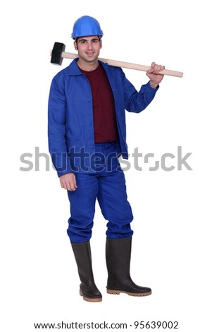 Man casually stood with sledge-hammer resting on shoulder - stock photo