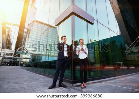 Man CEO is calling via mobile phone, while his female worker is thinking what to write in text message on cellphone. Two entrepreneur is using their cell telephones, while are waiting partner outdoors - stock photo