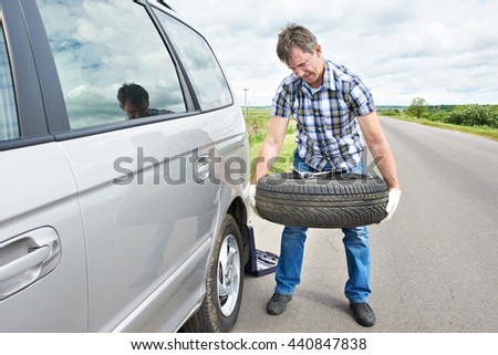 Man changing a spare tire of car on road