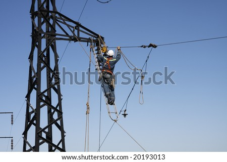 Man changing cable on high tension. - stock photo