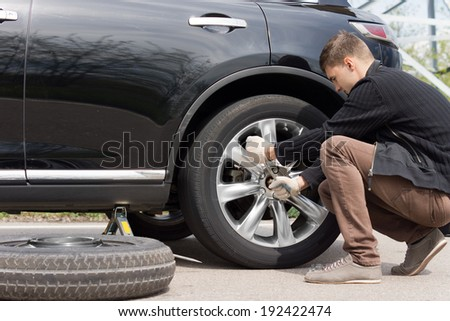 Man changing his spare wheel replacing the original tyre with a fixed puncture tightening the nuts with a wheel spanner - stock photo