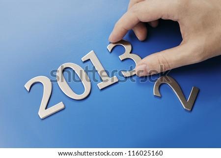 Man changing metallic numbers to year 2013. - stock photo