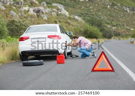 Man changing wheel after a car breakdown at the side of the road - stock photo