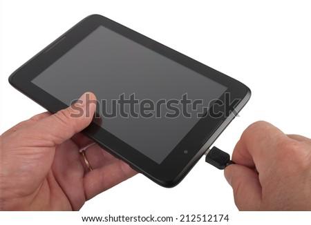 man charging black tablet, studio shot - stock photo