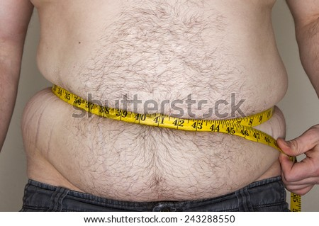 Man cheating on the weight loss tape by having it push in his fat - stock photo