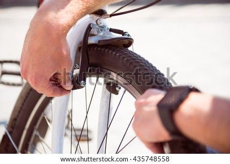 Man checking a wheel on his bike