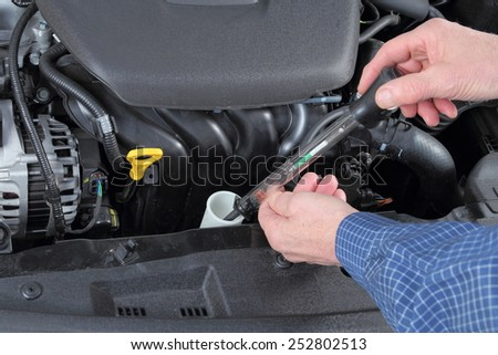 Man Checking Antifreeze in a Car coolant System