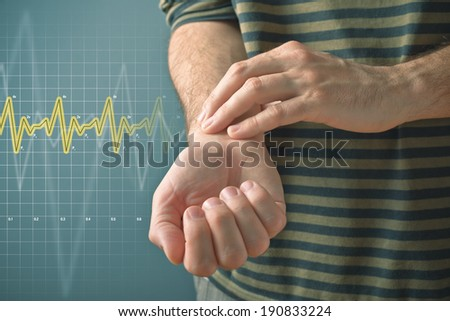 Man checking his pulse by pressing the wrist with fingers. Health issues concept. - stock photo