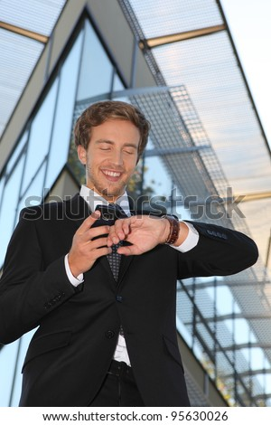 Man checking his watch against his cellphone - stock photo